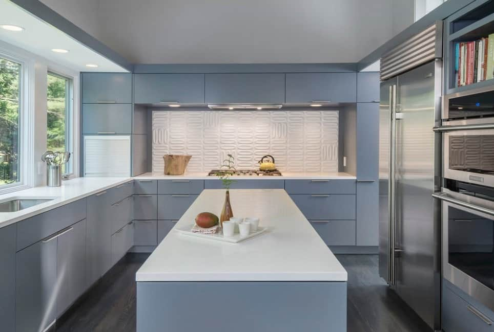 This kitchen offers gray kitchen counters and center island both with smooth white countertops. The room also features hardwood floors and stainless steel appliances.