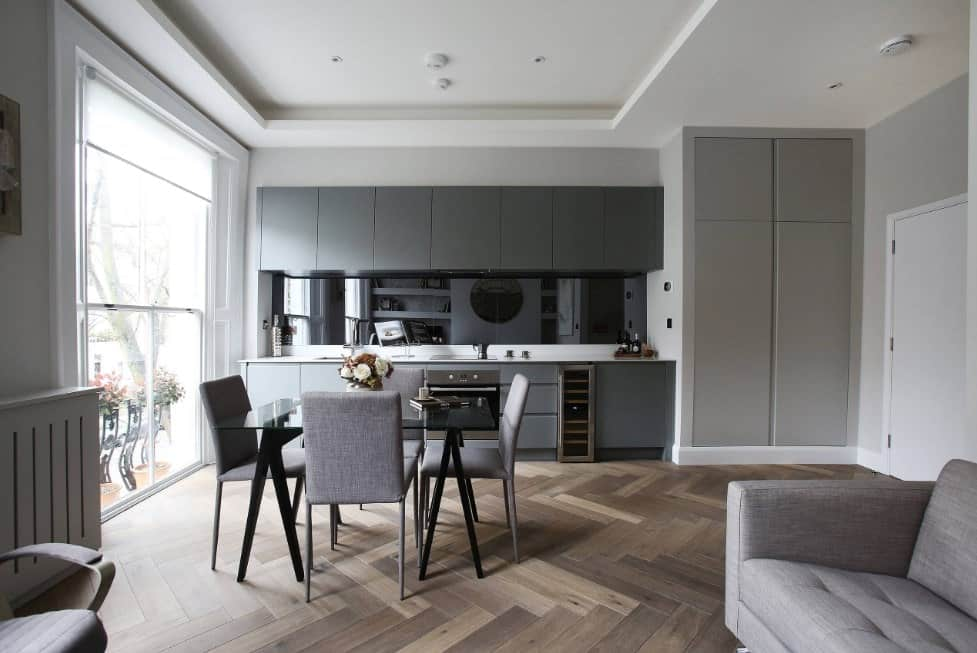 Single wall kitchen featuring herringbone hardwood floors, gray kitchen counters and a modish square dining table and chairs set under the white tray ceiling.