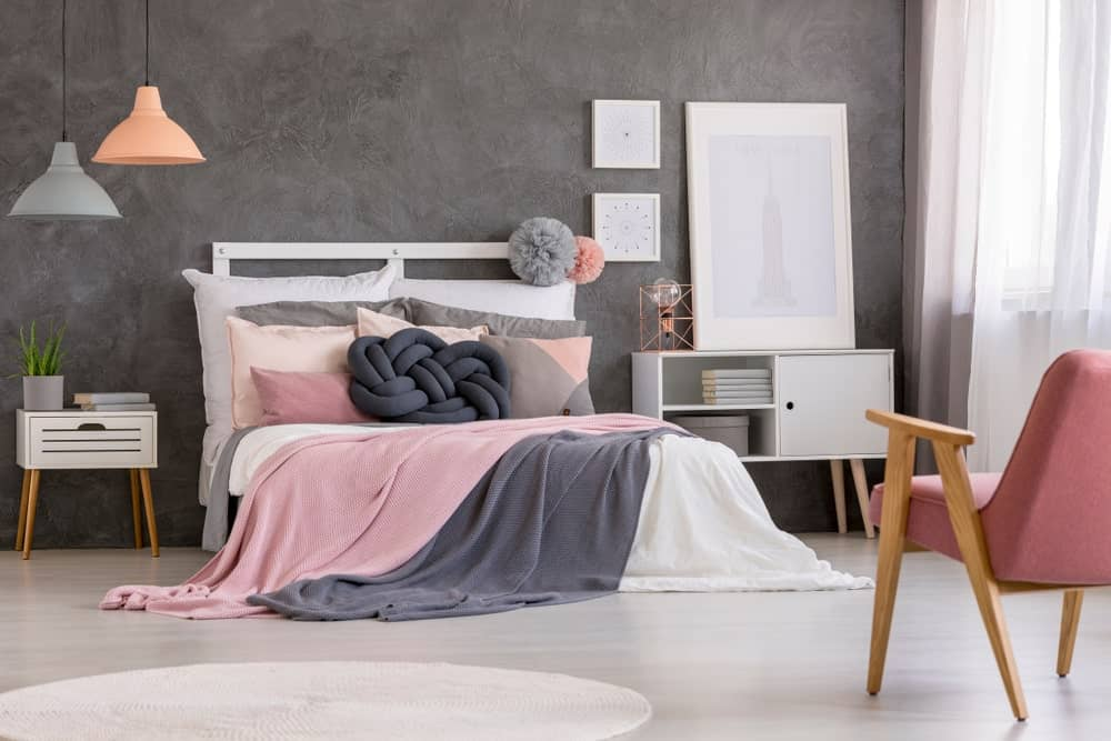 A primary bedroom with gray walls and white window curtains. The room also boasts a pink shade adding style to it.