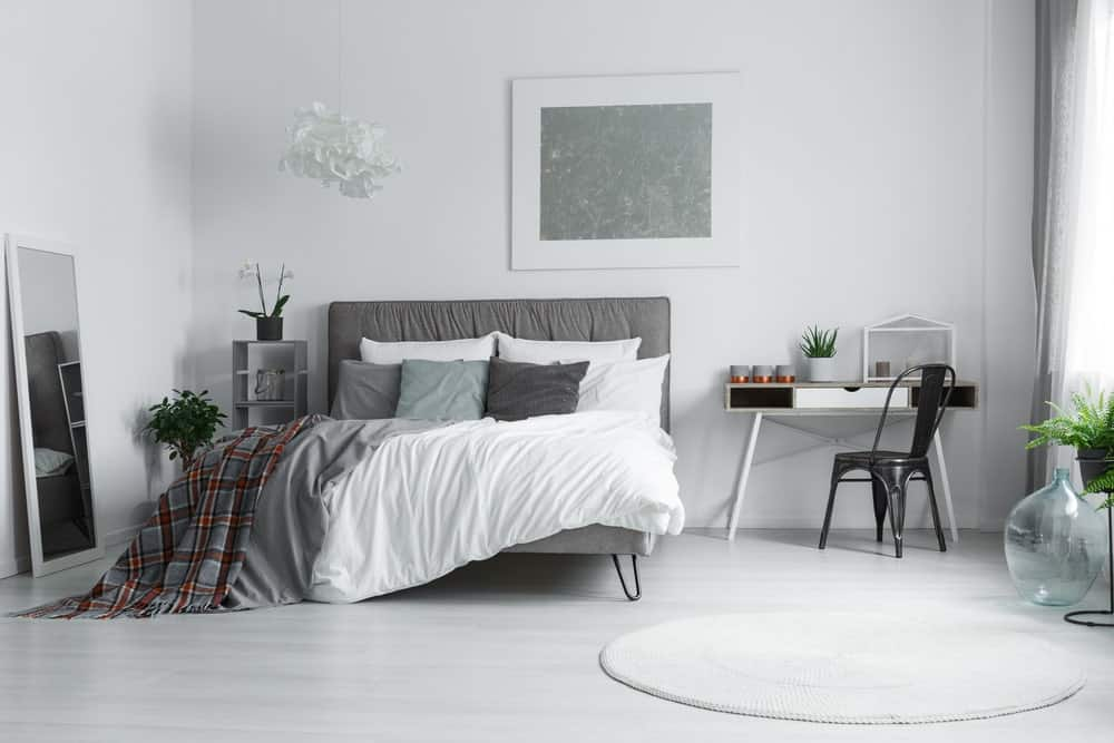 Gray master bedroom with a modern bed and a desk on the side. The flooring is topped by a round white rug.