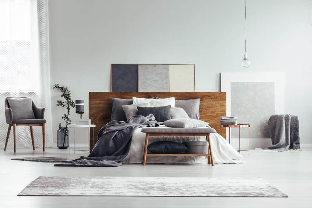 A focused shot at this primary bedroom's modern large bed surrounded by gray walls and floors.
