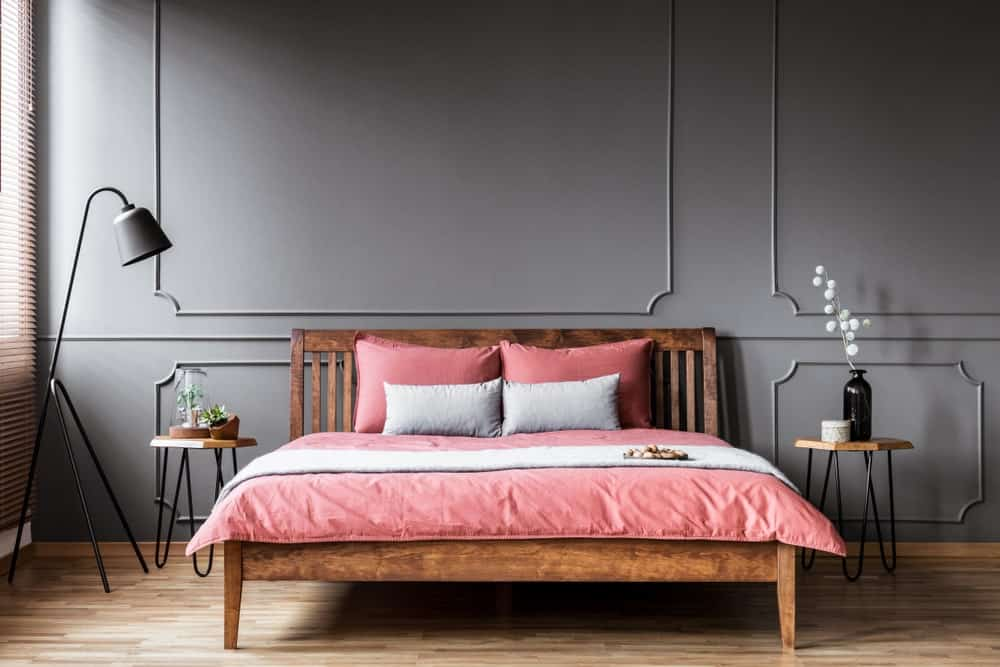 A primary bedroom with elegant gray walls and a large classy bed set on the room's hardwood flooring.