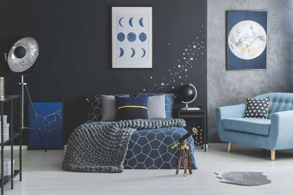 Contemporary primary bedroom with a very stylish black and gray walls along with its space-theme design.