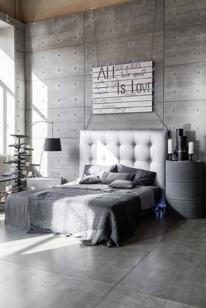Modern primary bedroom featuring gray walls, gray floors and a gray bed matching the gray side table.