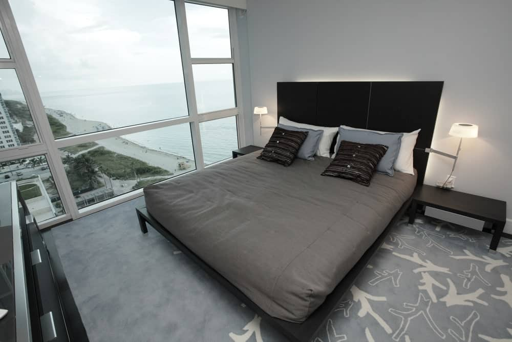 Modern master bedroom featuring a stylish black and gray bed set on a massive rug covering the black flooring.