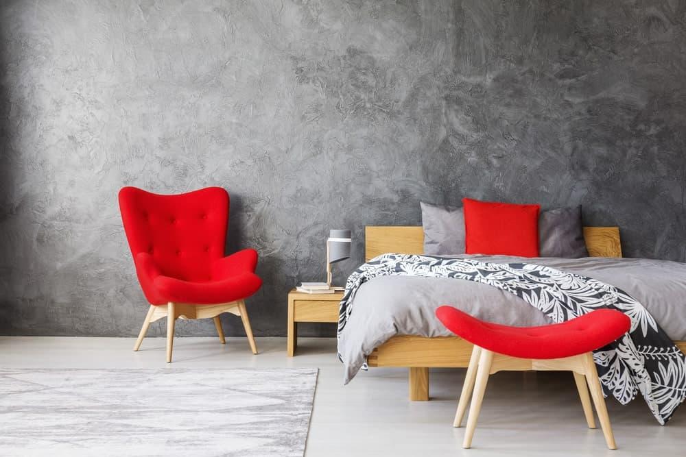 A primary bedroom with stylish gray walls and a red shade adding color to the room. The flooring is topped by a gray rug.