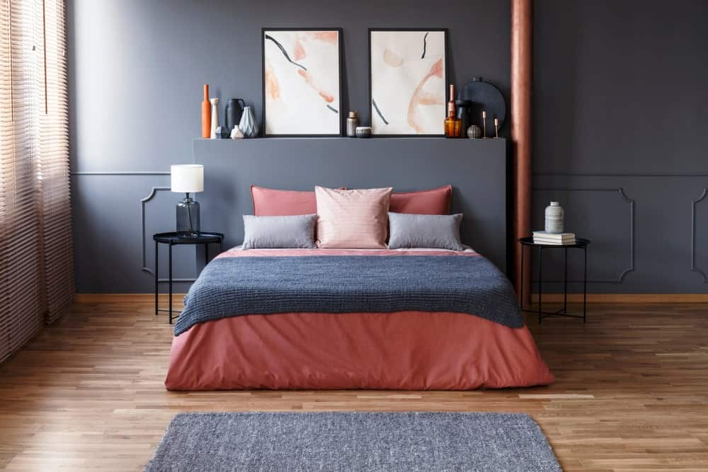 Contemporary primary bedroom with gray walls and hardwood floors topped by a gray rug.
