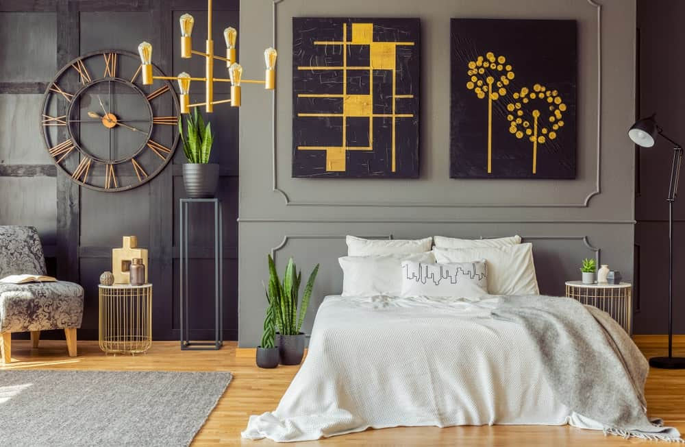 This primary bedroom features stylish walls and attractive wall decors, along with vinyl hardwood floors topped by a gray rug.