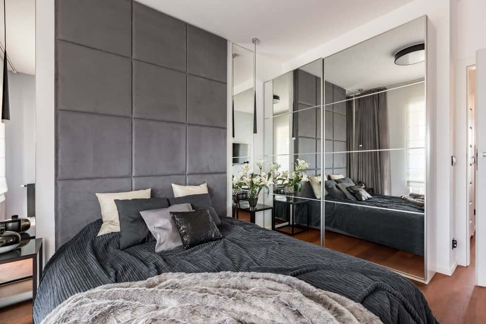 Modern primary bedroom with gray and black bed set on the room's hardwood flooring.