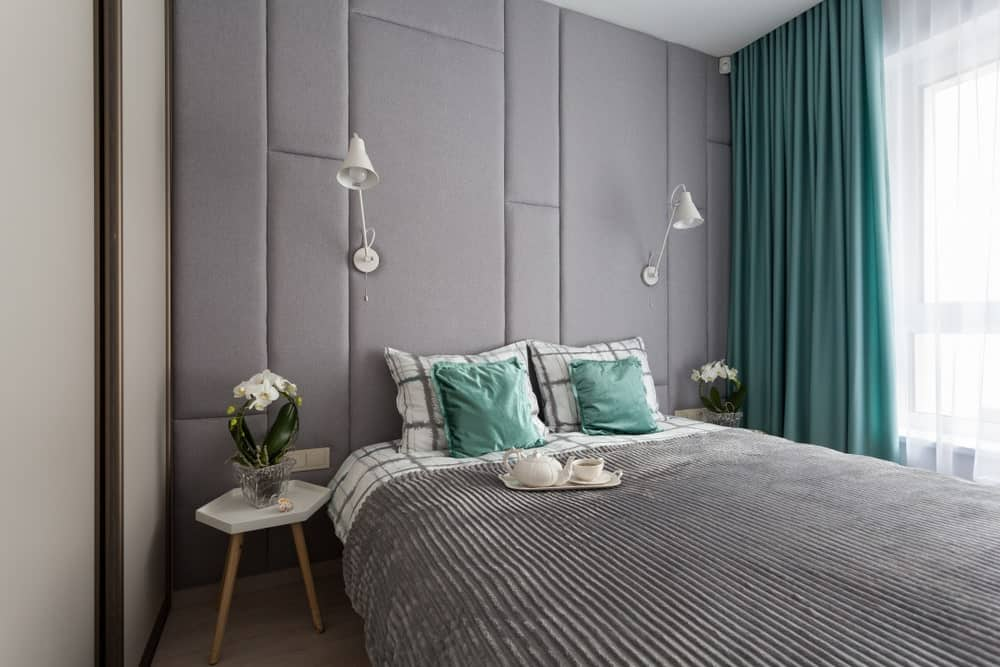 Small primary bedroom with a soft gray wall lighted by wall lights. The green window curtains add style to the room.