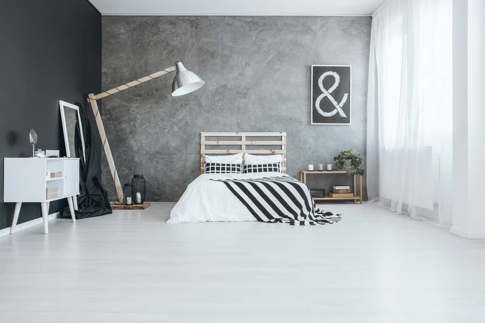 Contemporary primary bedroom with a combination of black and gray walls, along with a bed lighted by an attractive floor lamp.