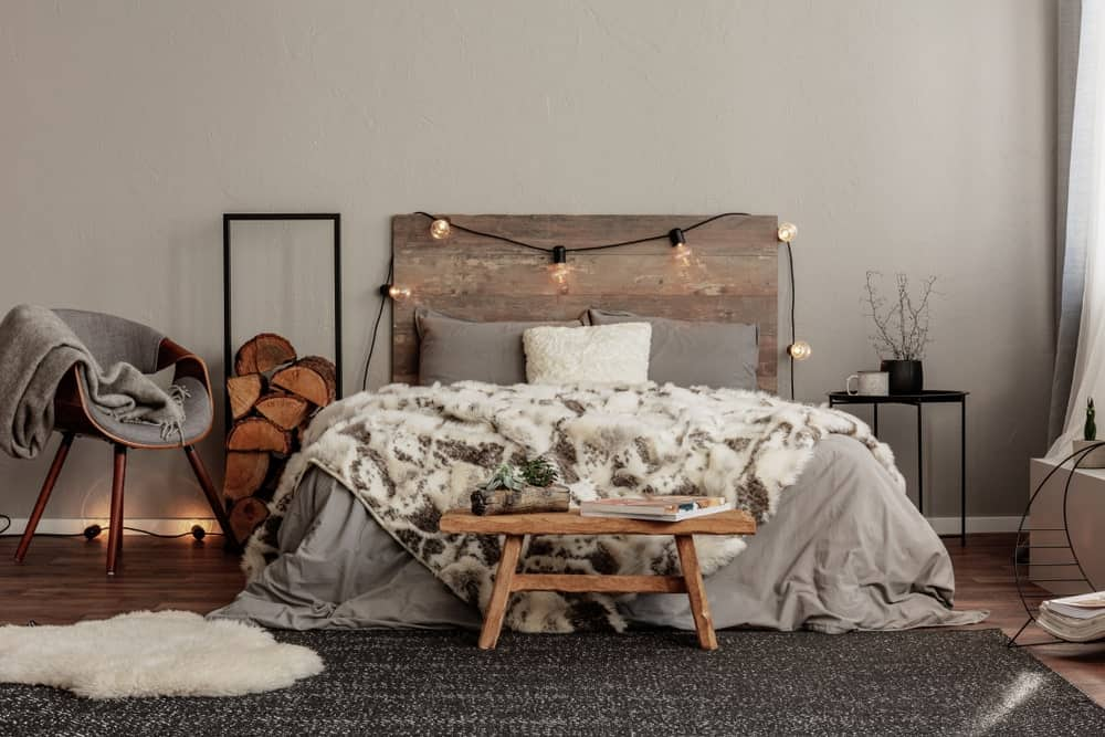This primary bedroom features hardwood floors, light gray walls and a rustic bed frame.