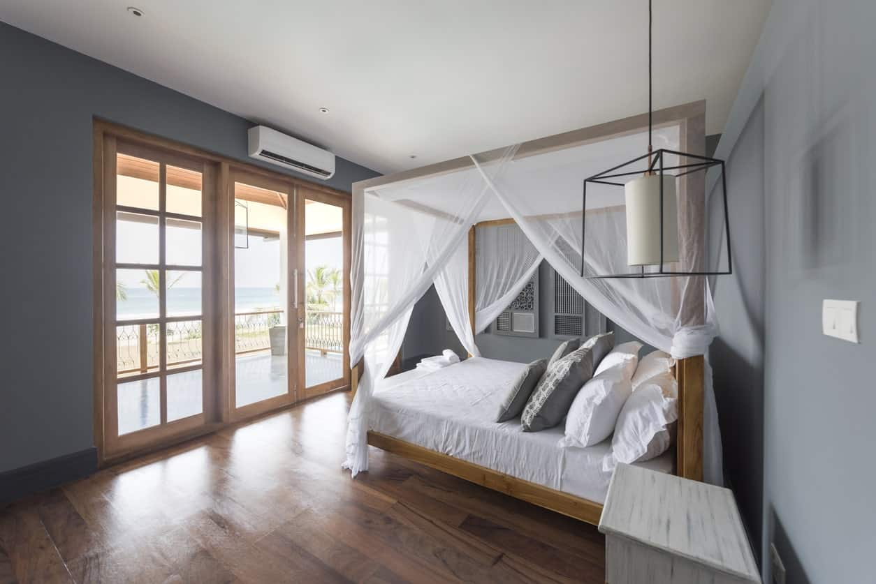 Medium-sized primary bedroom featuring hardwood floors and gray walls, along with a doorway leading to the home's veranda.