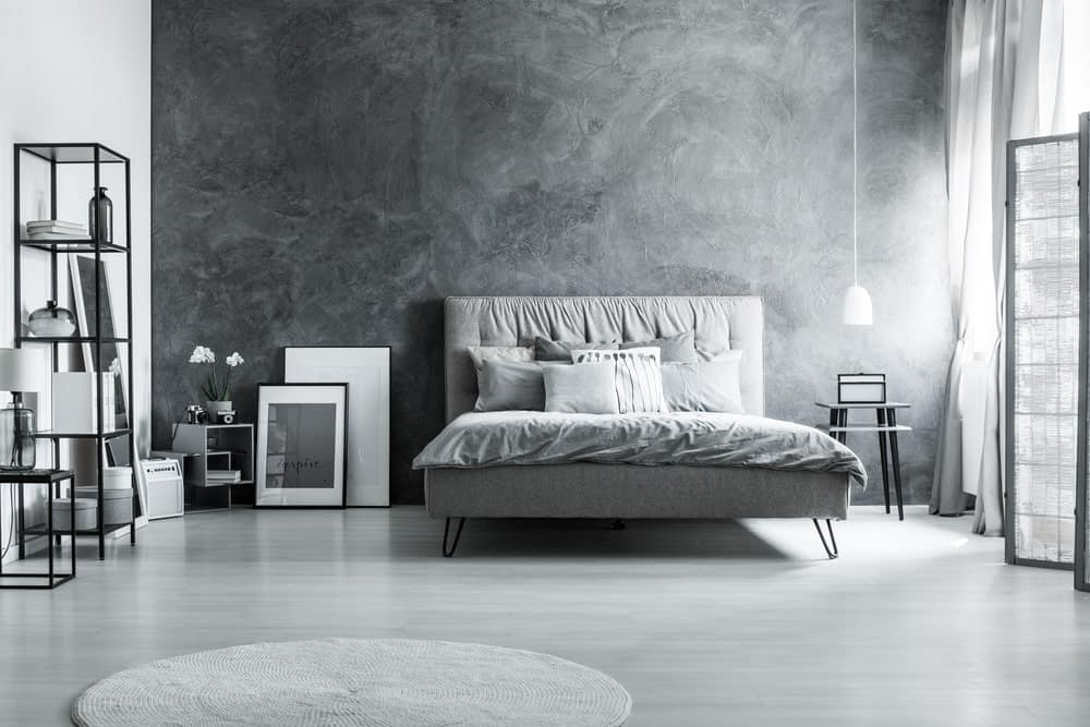 Contemporary primary bedroom with gray walls and floors, along with a gray large bed.