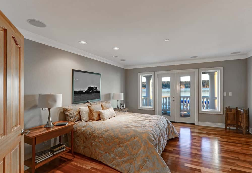 A primary bedroom with shiny vinyl floors and gray walls, along with a large classy bed with two table lamps on both sides.