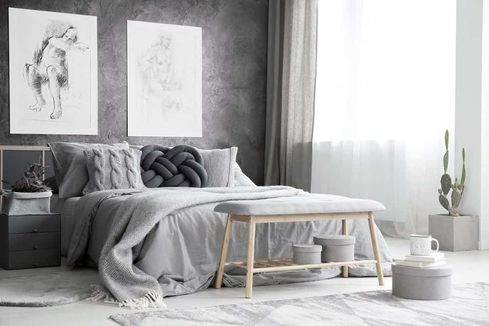 A primary bedroom featuring gray walls and a gray bed. The wall decors look absolutely artistic.