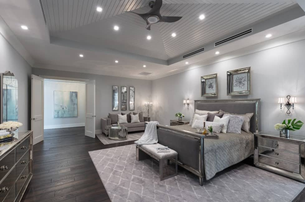 Large gray master bedroom featuring hardwood flooring and a tray ceiling. The room is lighted by wall sconces, recessed lights and a floor lamp.