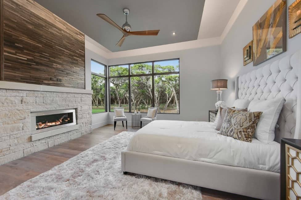 This master bedroom offers a large luxurious bed set on the hardwood flooring topped by a rug. The room has a fireplace and glass windows.