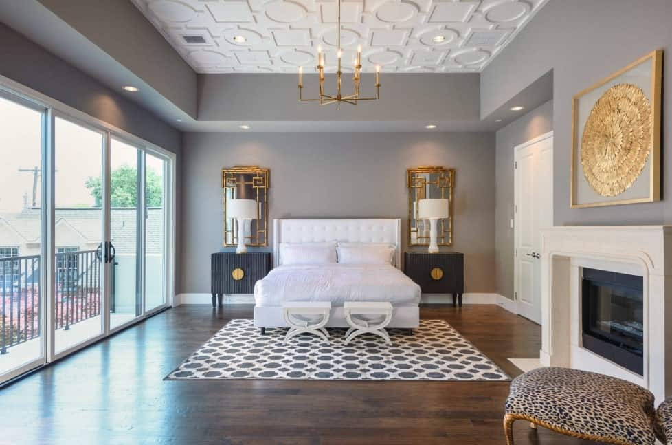 Modern primary bedroom featuring hardwood flooring, gray walls and a fireplace, along with a stunning ceiling lighted by a fabulous chandelier.