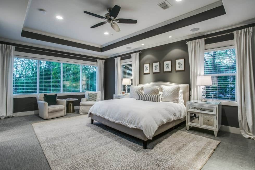 Master bedroom boasting a white and gray tray ceiling matching the walls and carpet flooring. The room has a large bed lighted by table lamps.