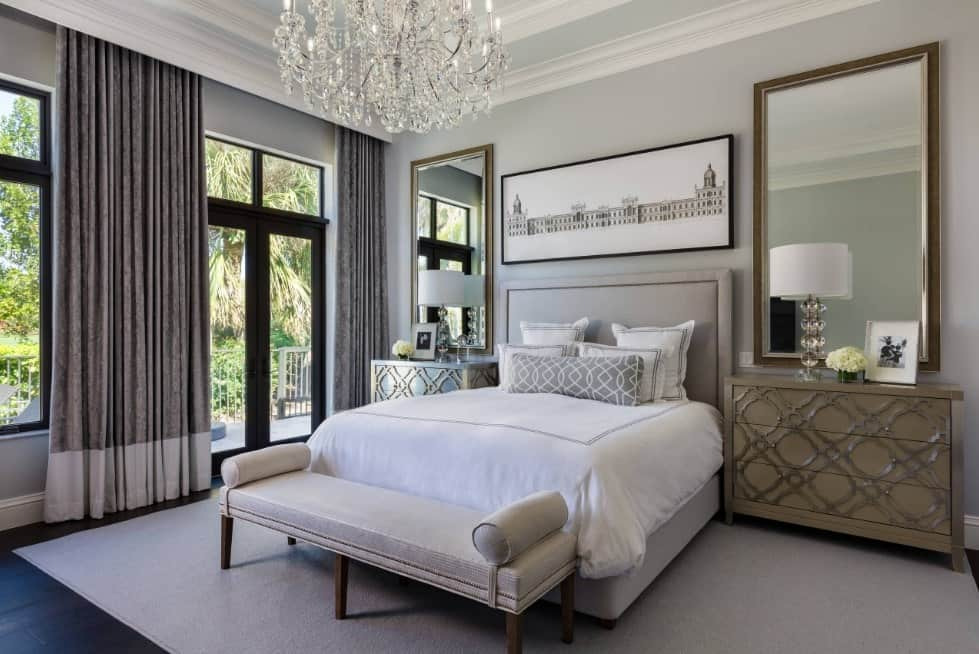Master bedroom with a comfy bed set on a rug covering the hardwood flooring. The room is lighted by a stunning chandelier.