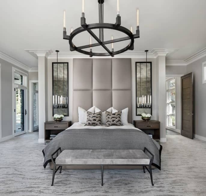 A master bedroom with a luxurious bed and stylish gray carpet flooring. The room's lighting looks absolutely magnificent as well.