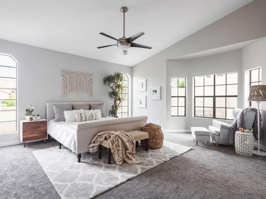 This primary bedroom features light gray walls and carpet flooring topped by a rug.