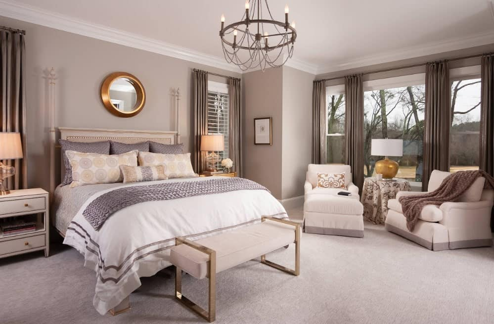 Master bedroom featuring a gorgeous bed lighted by two table lamps and a sitting area with a center table topped by a lamp. The room has carpet flooring.