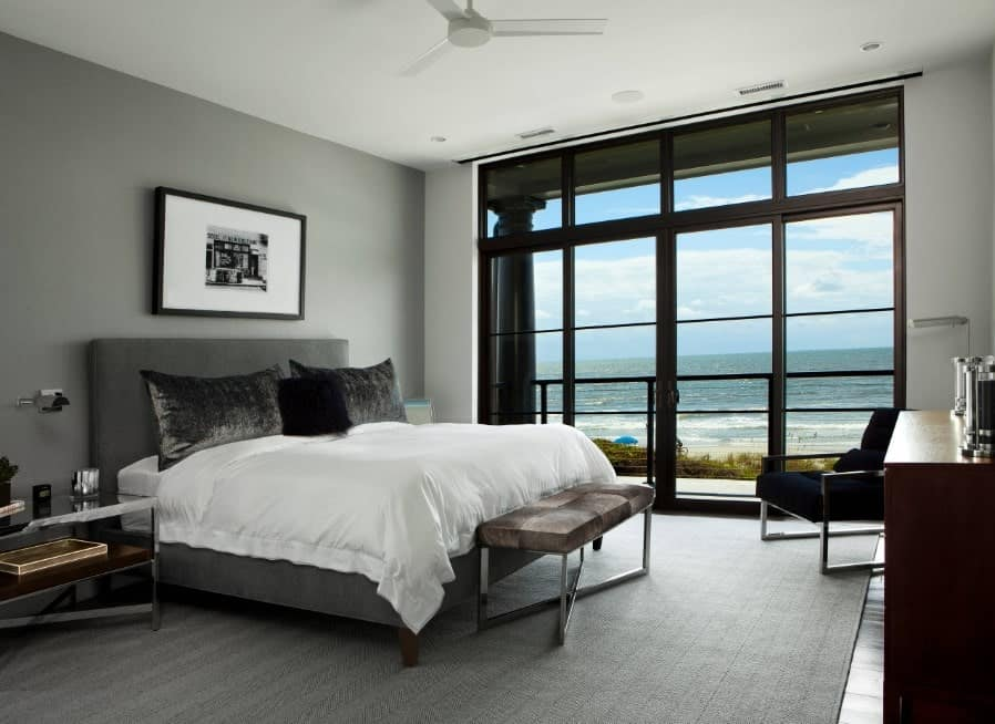 Modern master bedroom featuring a stylish gray bed set on a large gray rug. There a glass doorway leading to the home's terrace.