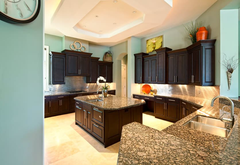 The blue-green in this kitchen is a bad choice. Nothing works here. The walls should be white in order to handle that deep, dark wood on all the cabinetry.