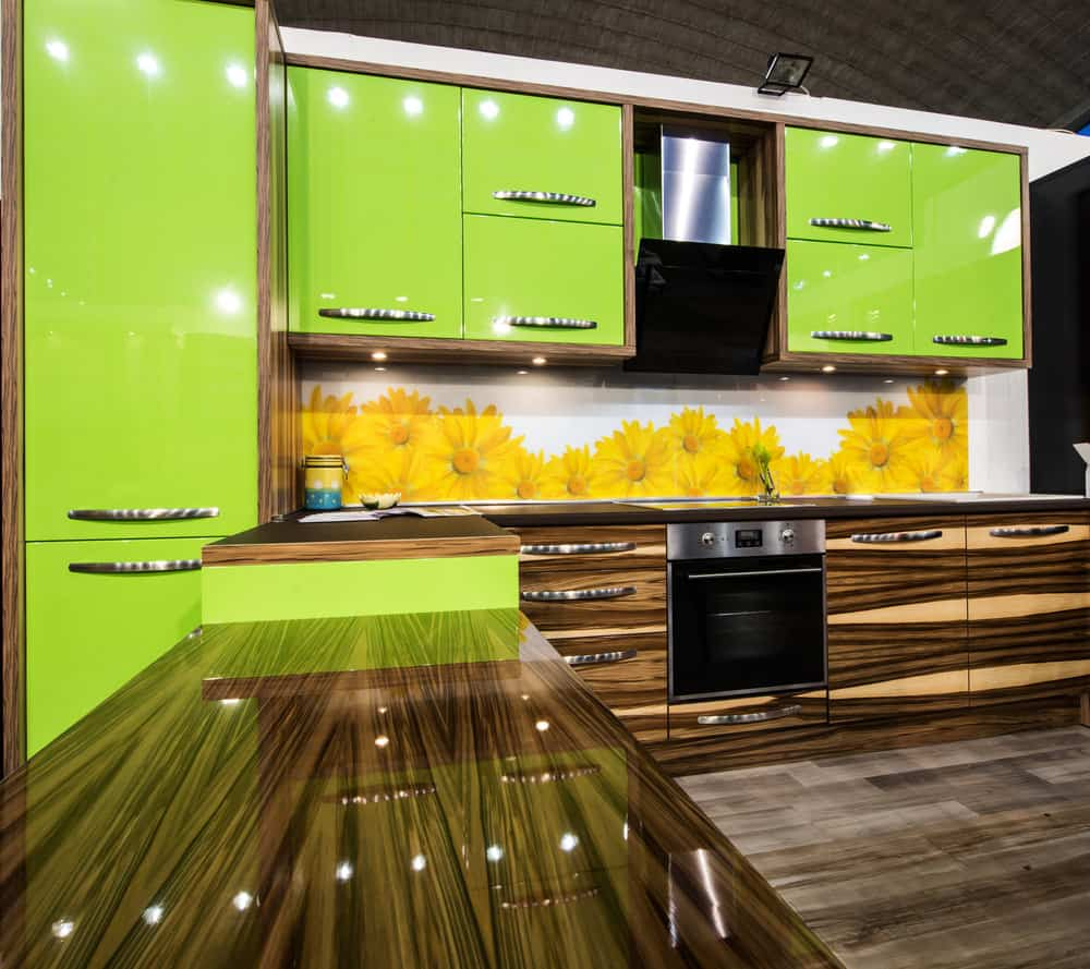 Another example of neon green cabinets - this time combined with glossy wood grain modern cabinetry that actually works. The flower backsplash definitely doesn't work.