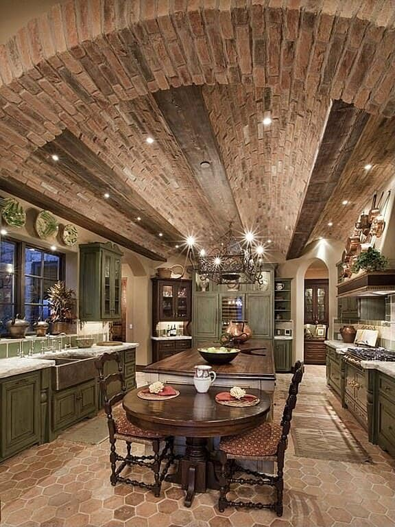 Stunning luxury cavernous kitchen with a barrel vault ceiling and dark green cabinetry. There is so much brown - brown tile flooring and brown brick ceiling along with a rich dark island and kitchen table that the dark green doesn't dominate but instead serves as an accent color.
