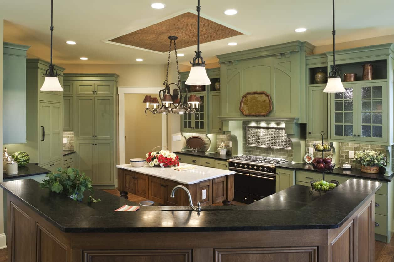 Here's our featured green kitchen that's luxury in size, features and design. The ornate green cabinetry works well and is tempered by two natural wood island and a white ceiling.