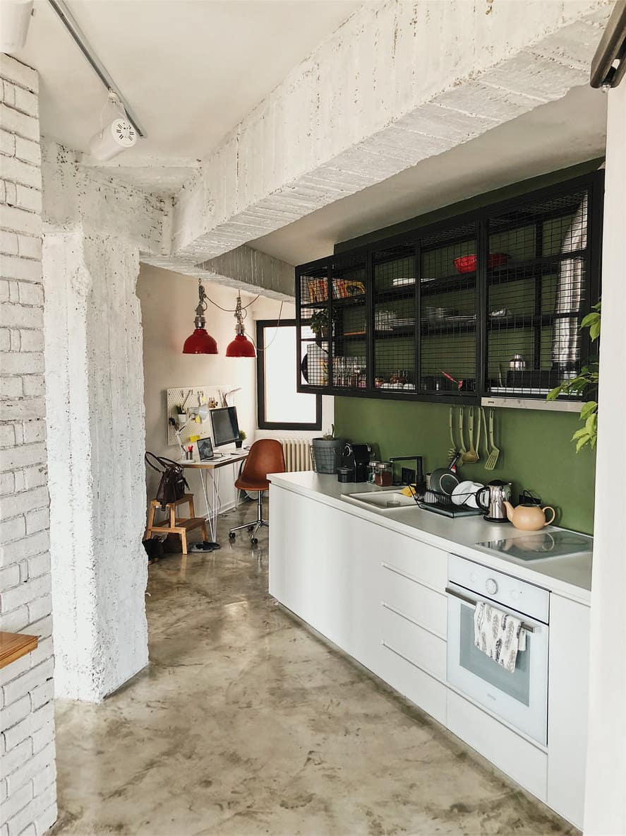 This is a loft apartment with a single line kitchen featuring a solid green wall which works pretty well. Again, all the white offset the green nicely.
