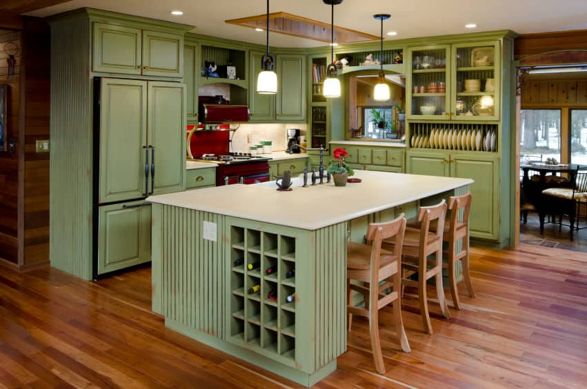 This is a green farmhouse kitchen design where all the cabinets are green but done in a distressed fashion so it works quite well with the type of cabinets and flooring.