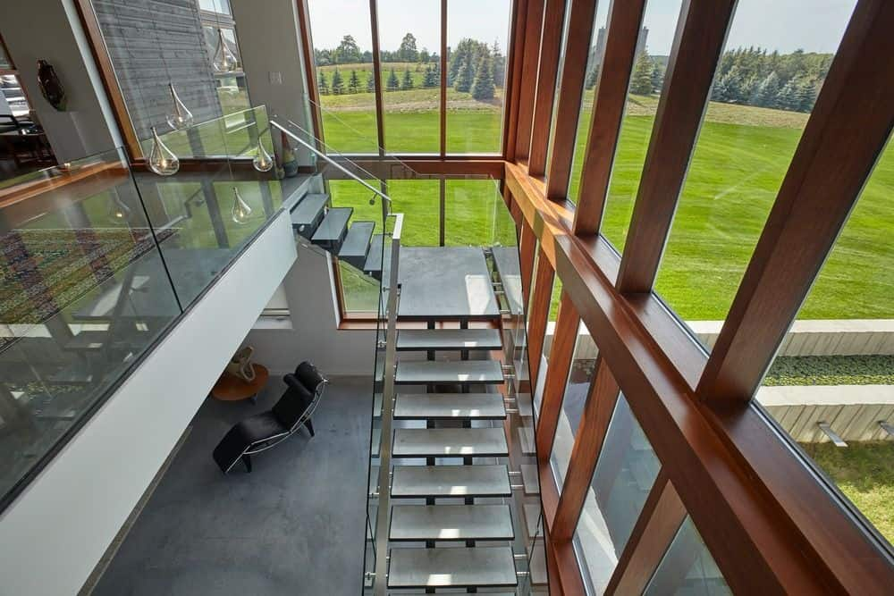 Modern staircase with open riser and glass balustrade complements the floor to ceiling windows overlooking a lovely outdoor scenery.