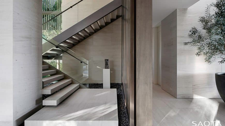 Open riser half-turn staircase with landing surrounded by pebbles. It features a frameless balustrade lined with a thin steel handrail.