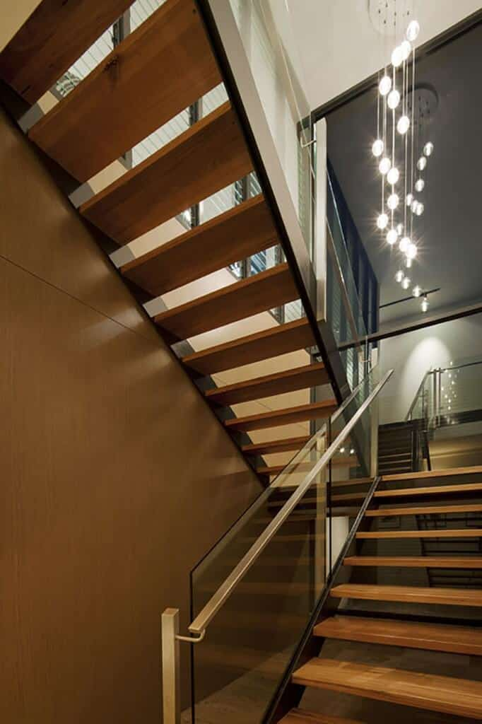 Wooden half-turn staircase with glass balustrade illuminated with bubble crystal ball pendant lights.