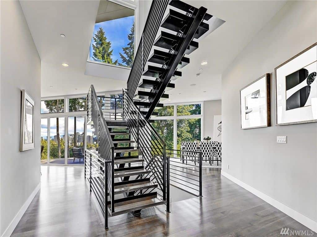 Black half-turn staircase with open riser and stainless steel balustrade along the gray hallway decorated with huge frames.