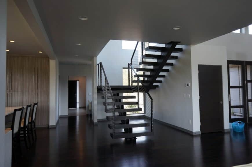 Black half-turn staircase with single stringer and thin steel railings against the white walls and hardwood flooring.