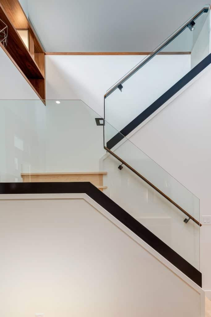 Cream half-turn staircase showcases a frameless glass balustrade and wooden handrail and treads against a white wall.