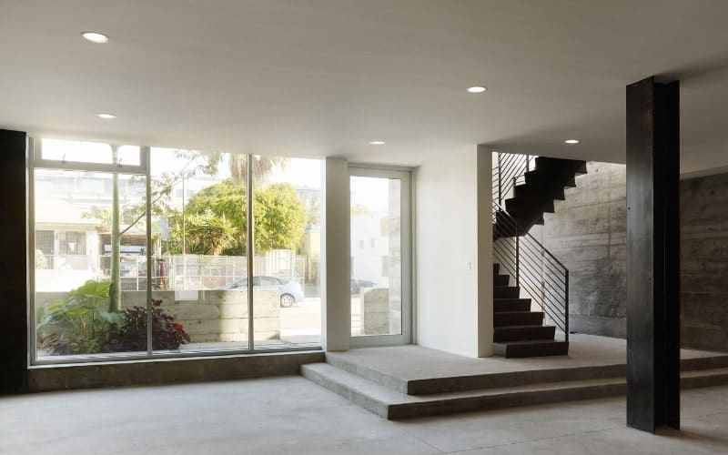 Spacious entrance hall with a concrete half-turn staircase in the corner featuring stainless steel railings.