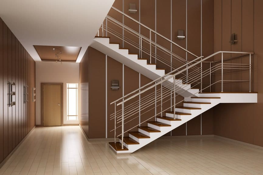 A two-tone half-turn staircase with stainless steel railing and wooden treads on a brown wall along a hallway.