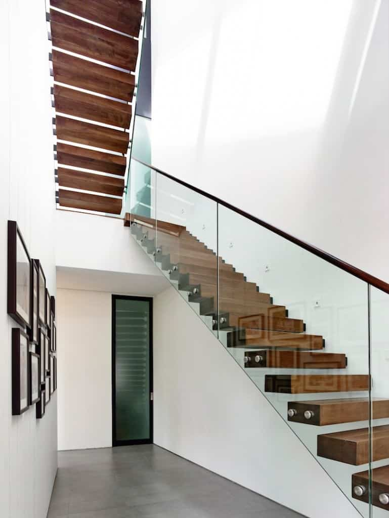 Tall half-turn staircase featuring wood handrail and glass railing along the white walls.