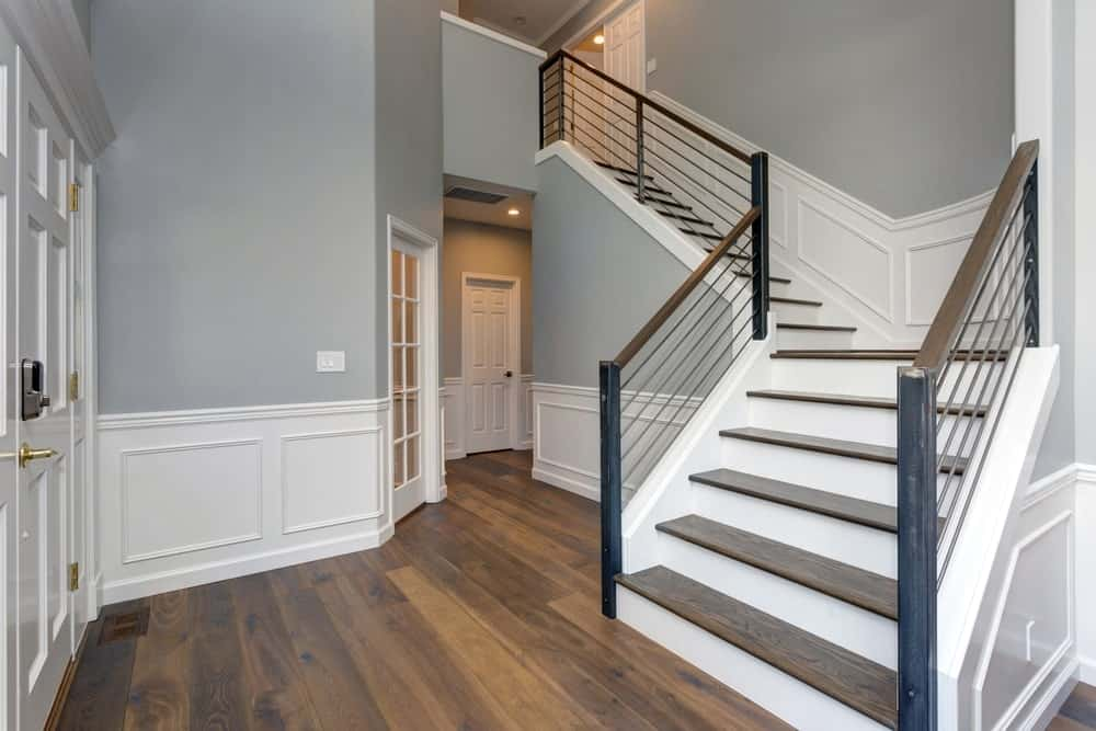 A half-turn staircase with white riser and wooden treads along with stainless steel railings on the wainscoted walls.