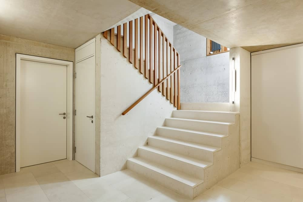 White tiled half-turn staircase with a thin hand railing on the first level and wooden spindles on the second.