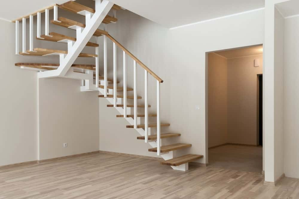 Half-turn staircase with white straight single stringer and spindles along with wooden treads and railing complementing the white walls and hardwood flooring.