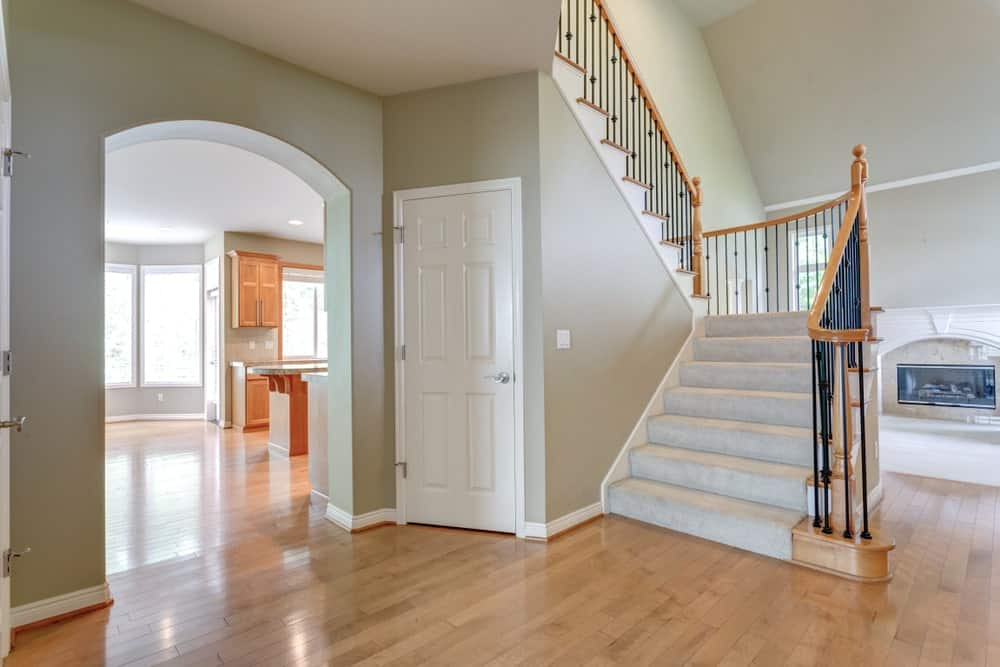 An open archway that leads to the white half-turn staircase with wrought iron spindles and wooden railings. It is beautifully covered with gray carpet.