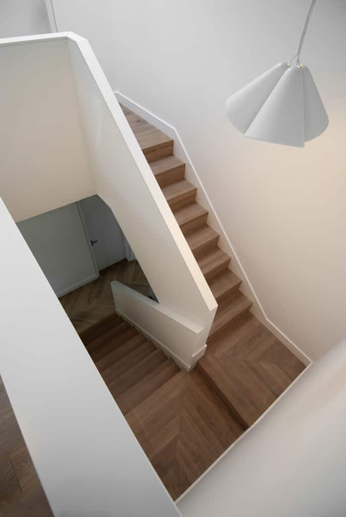 High angle view of a dark wooden half-turn staircase with balustrade wall illuminated by a white pendant light.