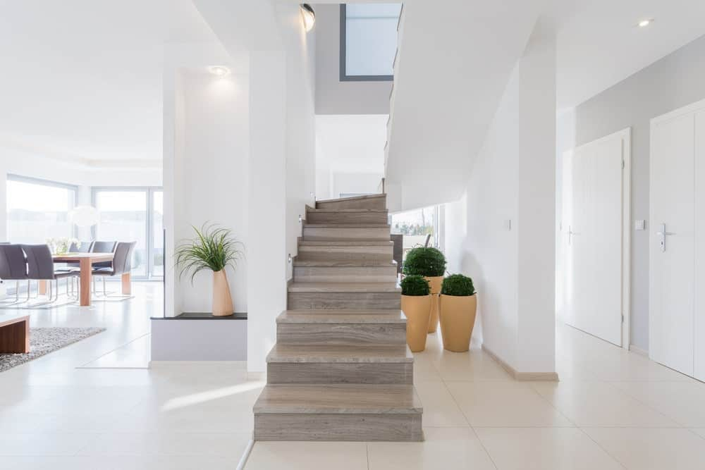 Light wood half-turn staircase with no railings surrounded with white walls and tiled flooring. It is accented with potted plants beneath it.